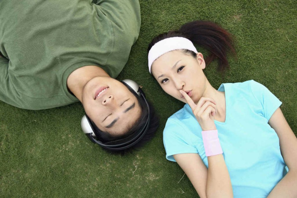 girl and guy with headphones relaxing